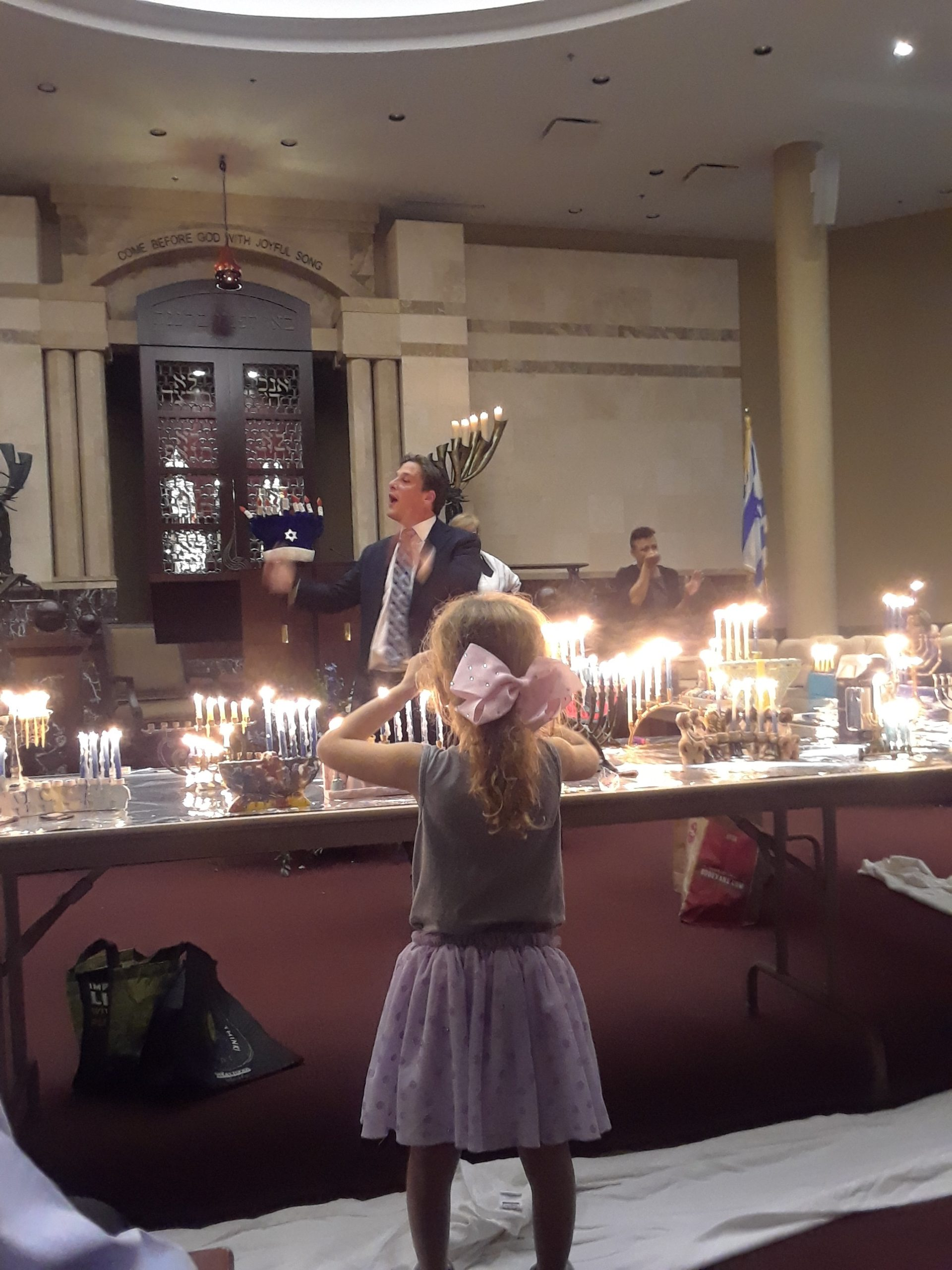 Ellie Durbin listening to Rabbi DUrbin During Chanukah candle lighting Service